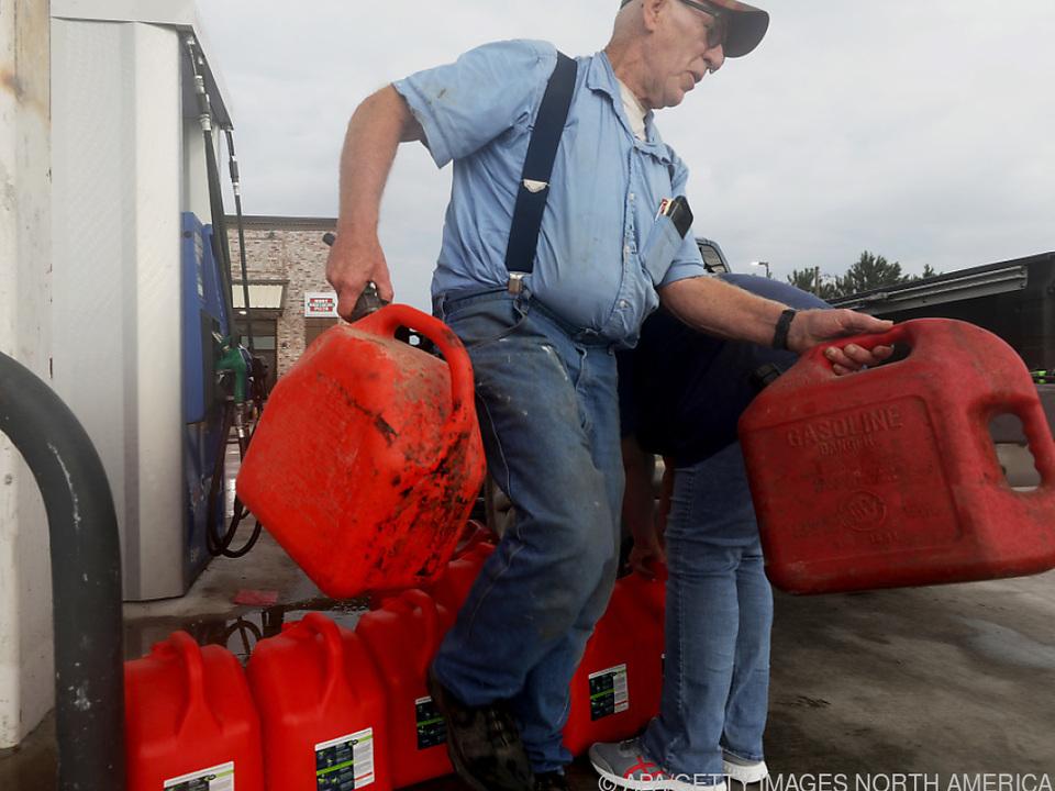 Die Menschen holen Benzin für ihre Stromgeneratoren