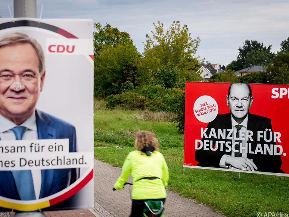 Eine Radfahrerin passiert Plakate der Kanzlerkandidaten in Berlin
