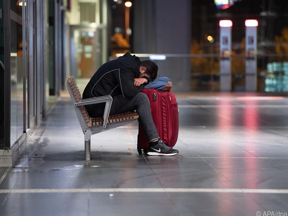 Mann mit Gepäck schläft auf Berliner Hauptbahnhof